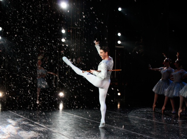 Christopher Ruud as the Snow King with Hat and Cane and a Chorus Line of Snow Flakes upstage of him.